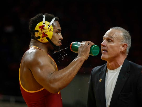 Iowa State freshman Sam Colbray (197 pounds) talks with coach Kevin Dresser during the team's matchup with Wyoming earlier this season. Colbray's win Sunday was key in the Cyclones' victory over West Virginia.