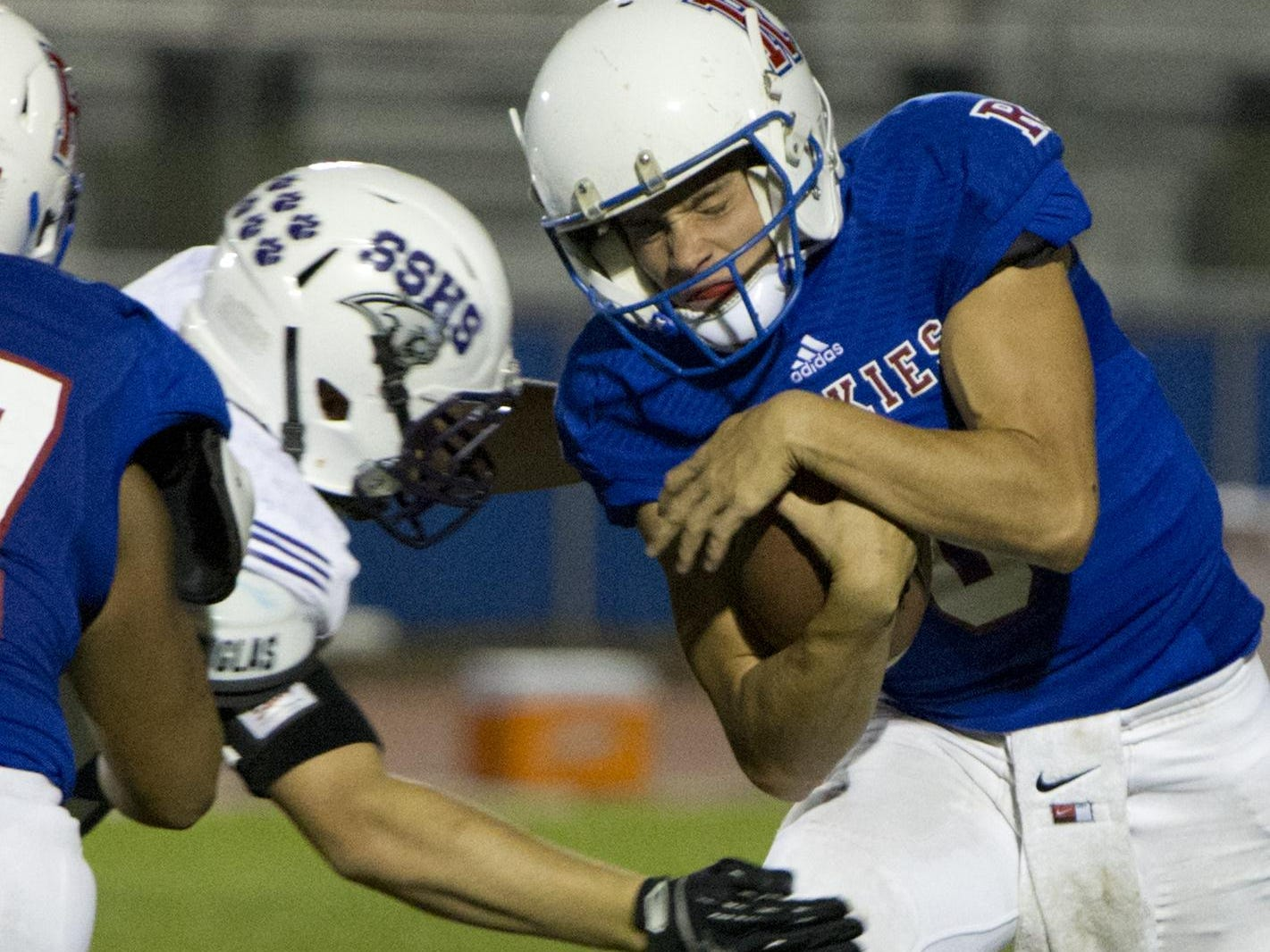 Reno quarterback Isaac Terrasas is hit by a Spanish Springs defender on Friday.