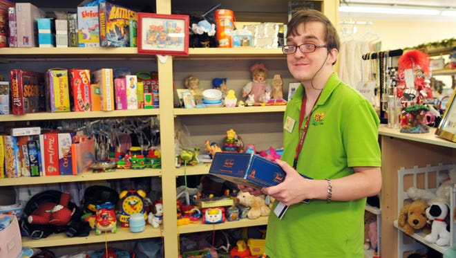 Jack Sellars working with shelves of games and toys.