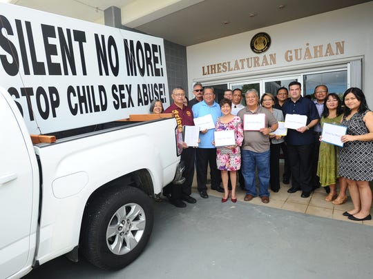 Joe Santos, second from left, Silent No More campaign founder, is photographed with Concerned Catholics of Guam members, island lawmakers, alledged sexual abuse victims and other supporters after a brief ceremony at the Guam Legislature in Hagåtña on Thursday, Sept. 8.