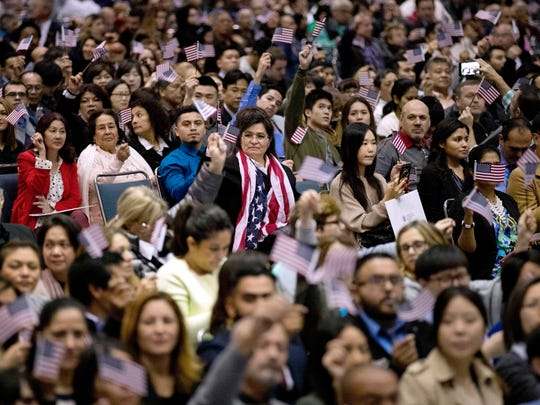 In this Wednesday, Feb. 15, 2017, photo, people wave U.S. flags during a naturalization ceremony at the Los Angeles Convention Center, in Los Angeles. Since Trump's immigration enforcement order and travel ban, immigrants have been rushing to prepare applications to become Americans. Advocates in Los Angeles, Maryland and New York catering to diverse immigrant communities from Latin America, Asia and the Middle East all said they've been fielding a rising number of questions about how to become a U.S. citizen.