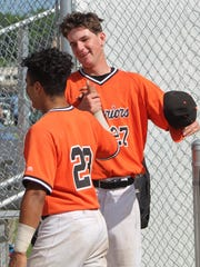 Rice senior pitcher Jack Brockhaus (27), the winning pitcher in the district title game who earned a save in the first game, shakes hands with teammate Gabe Sotres after winning the district title Saturday.