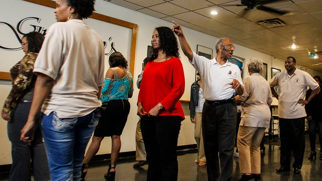 Sterling Armstrong of Lansing, middle, teaches students during his 'Ballroom Tuesdays' at Gregory's in Lansing.