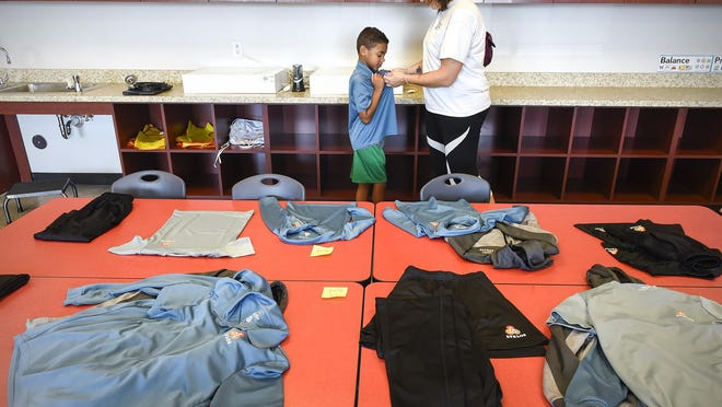 Anthony Clinton, 7, tries on uniforms with his mom Angela Tuesday, Aug. 29, at Athlos Academy of St. Cloud. Students are required to wear uniforms and this is a chance to see all the styles and try on sizes. The school has about 800 students enrolled this fall and classes start Tuesday, Sept. 5.