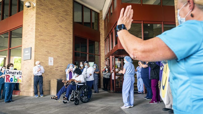 Robin Eaton is cheered by staff at Novant Health Forsyth Medical Center as she leaves the hospital after recovering from COVID-19 on Thursday in Winston-Salem.