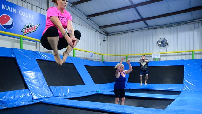 TOP: Jessica Liston works out during a recent Air-obics class at Flippin' Family Fun. The intense trampoline workout throws in jumping jacks, high jumps with kicks, burpees, lunges and other aerobic moves in a fast-paced setting.
