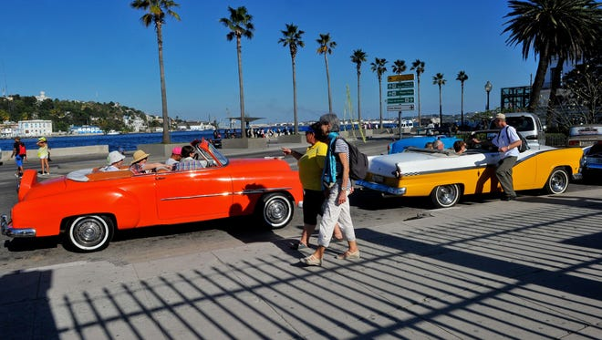 Tourists from the United States are seen in old American cars in Havana, on April 6, 2015.