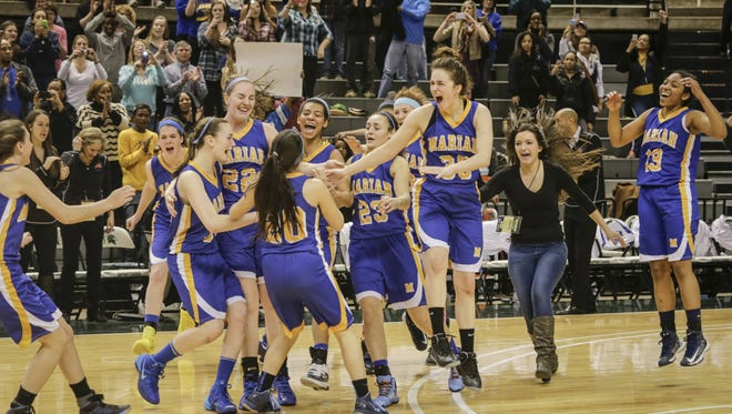 Birmingham Marian players celebrate their Class A state final game, winning 44-26 against Canton at the Breslin Center in East Lansing on March 15, 2014.