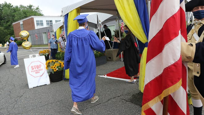 Members of the Lexington High School Class of 2020 got out of their cars and individually walked up to receive their diplomas Monday, June 29, 2020. Wicked Local Staff Photo/Ann Ringwood]