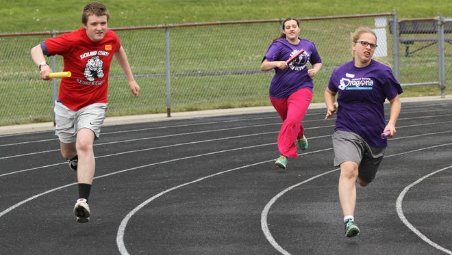 Nick Foglesmg (left to right), Lakota Muston and Zoey Vagner compete in the 4 by 100 meter relay during the area three Special Olympics competition at Lexington High School on Saturday.
