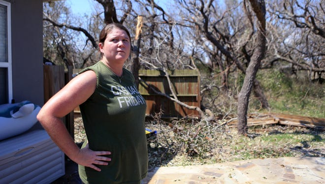 Andrea Brewington surveys her backyard in Rockport, while friends from San Antonio and Houston help clean up several trees that fell on her property on Thursday, Aug. 31, 2017.