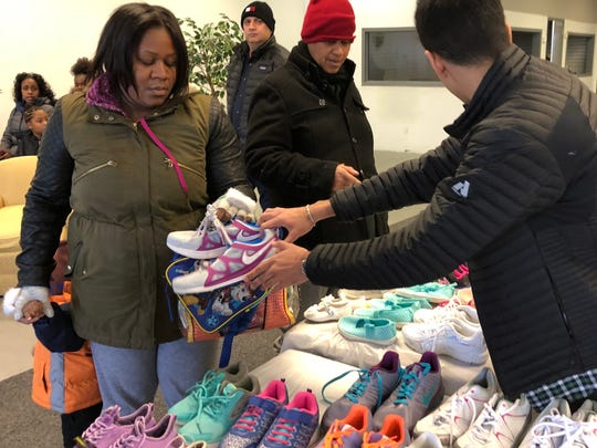 Prateek Bhola shares his shoes with folks at the Phillip House Mission in Detroit.