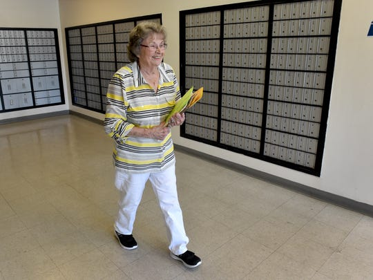 Tobey Bowers, of Fillmore, picks up mail from her post office box Thursday. Bowers plans to return Friday for a special postmark.