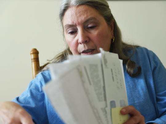 Janie Clark goes through her husband Ansol's medical bills in her Knoxville dining room on Wednesday, March 22, 2017. Ansol worked on clean up efforts of the January 2008 Kingston coal ash spill, and claims many of his illnesses are due to the working conditions he experienced there.