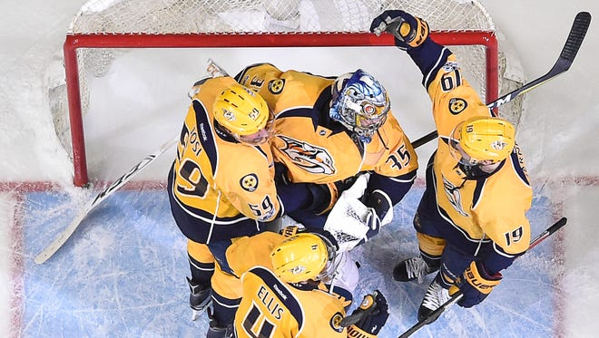 Nashville Predators defenseman Ryan Ellis (4), defenseman Roman Josi (59) and center Calle Jarnkrok (19) congratulate goalie Pekka Rinne (35) after their 3 to 1 victory against the St. Louis Blues of game six to close out  the second round NHL Stanley Cup Playoffs four games to two at the Bridgestone Arena  Sunday, May 7, 2017, in Nashville, Tenn.