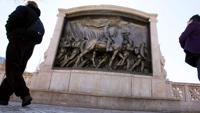 """FILE - In this March 26, 2011, file photo, people walk past the memorial to Union Col. Robert Gould Shaw and the 54th Massachusetts Volunteer Infantry Regiment, near the Statehouse in Boston. Amid the national reckoning on racism in July 2020, the memorial to the first Black regiment of the Union Army, the Civil War unit popularized in the movie """"Glory,"""" is facing scrutiny."""
