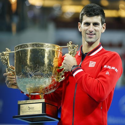 Novak Djokovic poses with trophies during the medal