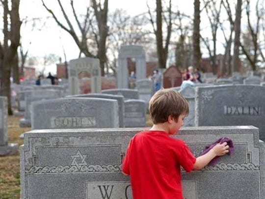 FILE - In this Wednesday, Feb. 22, 2017 file photo, Theo Richmond cleans a headstone at the Chesed Shel Emeth Cemetery in University City, Mo. In a Thursday, March 23, 2017 interview, Jonathan Greenblatt, chief executive of the Anti-Defamation League, said anti-Semitism remained a serious concern, pointing to recent incidents around the country.