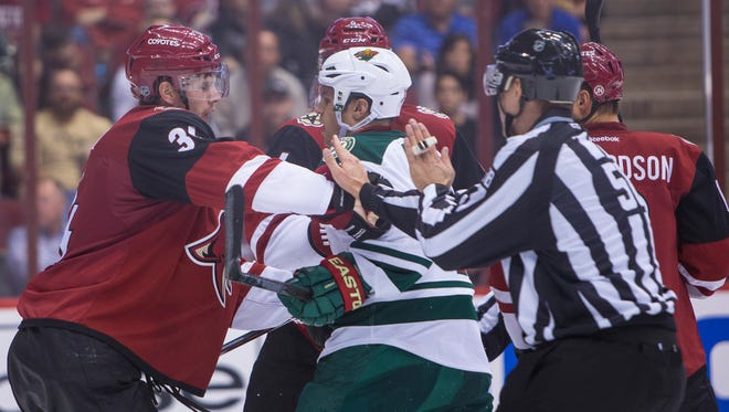 Coyotes' Klas Dahlbeck (left) pushes Wild's Zach Parise at Gila River Arena in Glendale on October 15, 2015.