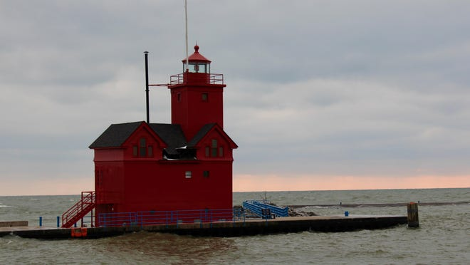 Waves crash against the Holland Harbor Light in Feb. 2020. According to the U.S. Army Corps of Engineers, water levels in Lake Michigan could drop slightly by Aug. 3.