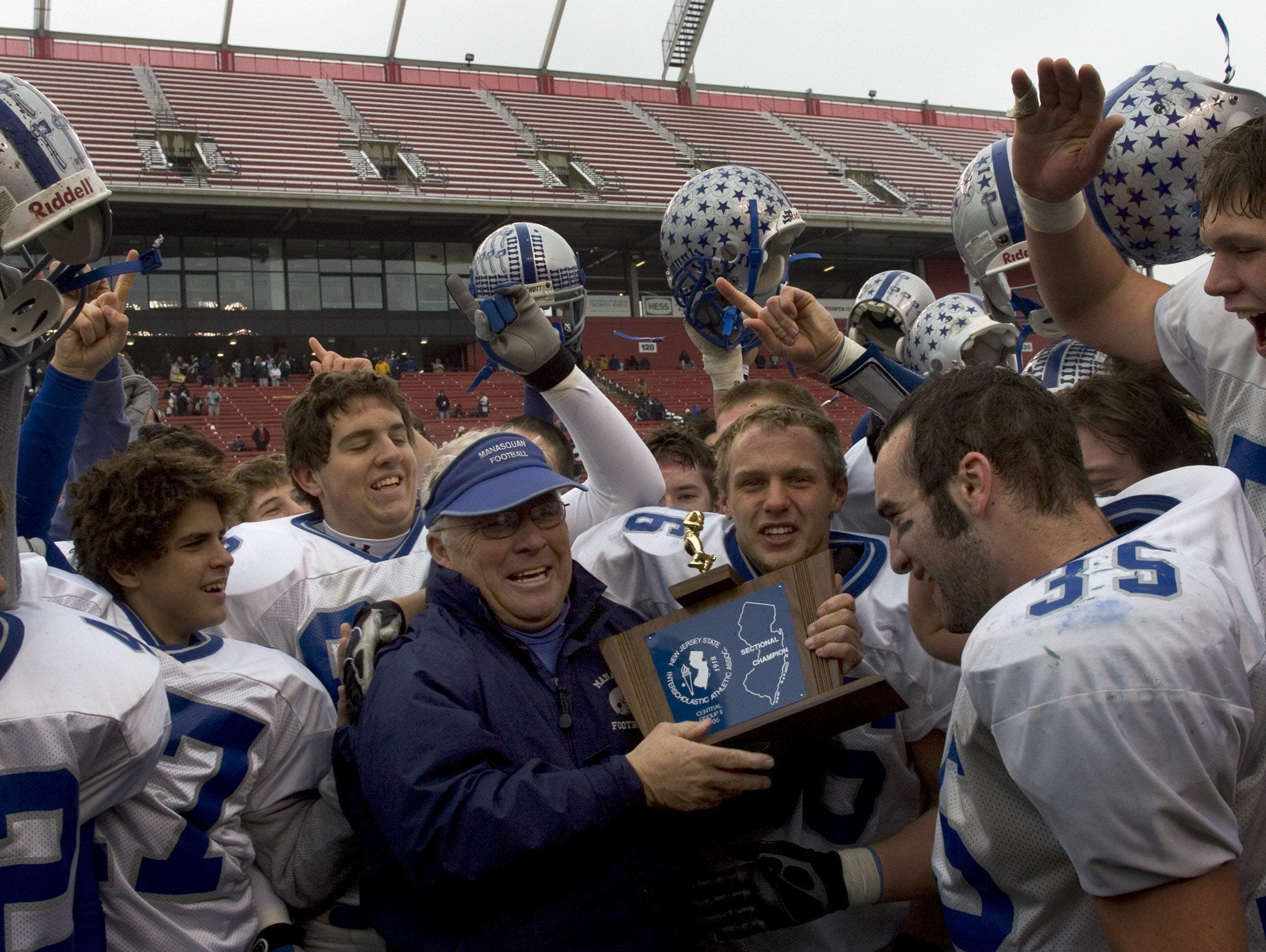 Manasquan coach Vic Kubu holds up championship trophy in 2005. Kubu coaches seven teams to unbeaten seasons over the years.