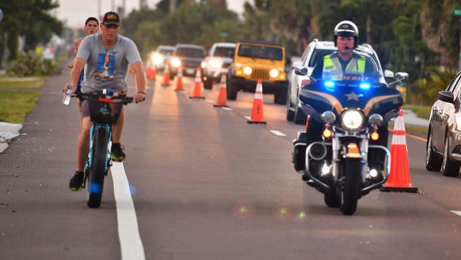 Thousands of runners, many dressed in costumes, made their way through Cocoa Beach at dawn Sunday morning for the Ron Jon Cocoa Beach Half Marathon. Race director Mitch Varnes leads the half marathon on his bike, escorted by a BCSO motor deputy followed closely by lead runner early in the race.