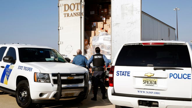 In this Monday, Feb. 6, 2017, photo, New Jersey State Police troopers look in the trailer of a truck flagged for further inspection at the Greenwich truck weigh station on Interstate 78, in Greenwich Township, N.J. The New Jersey State Police operate the weigh station and often check contents of trucks and trailers. (AP Photo/Mel Evans)