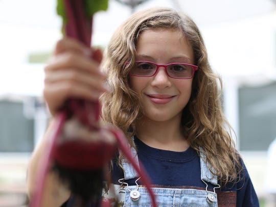 Addison Marusic holds up a beet she harvested from