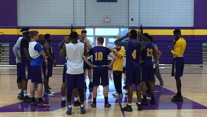LSUA Men's Basketball Coach Larry Cordaro (center in gold shirt) meets with his players at a recent practice.