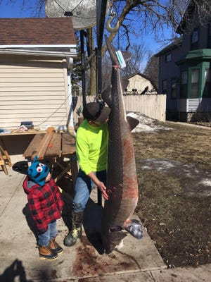 John Leroy kisses his sturgeon on Tuesday. It weighed 149.4 pounds.