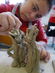 Jasmine Rice puts the final touches on clay figures