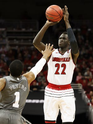 U of L's Deng Adel (22) hit a 3-point shot against Mississippi State's Lamar Peters (1) during the NIT at the Yum Center in Louisville.    Mar. 20, 2018