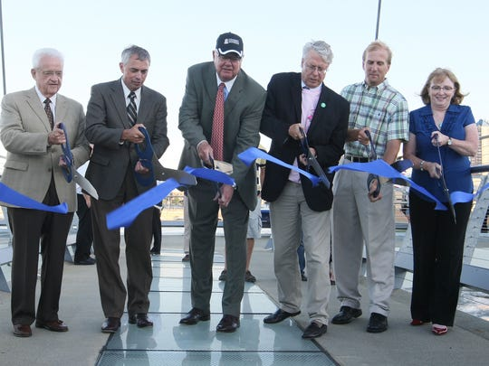 The Center Street Bridge opened with a ribbon cutting, a few ceremonial crossings and then a large mass of humanity made their way across the bridge to explore it from many angles Monday evening. Fireworks were postponed due to high wind and rising water levels. Cutting the ribbon are from left Leonard Boswell, Larry Zimpleman, Barry Griswell, Frank Cownie, Robert Cramer and Mary O'Keefe.