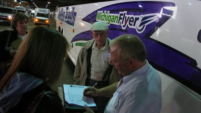 Michigan Flyer bus driver Lonnie Hoyt checks passengers names as they board his bus at Detroit Metro Airport. The airport recently relocated the drop-off and pick-up location for the Flyer bus and the writer advocates moving it back to its old location.