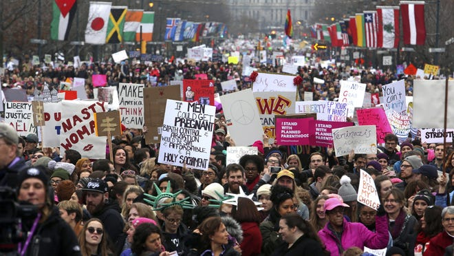 """FILE - In this Jan. 21, 2017, file photo, thousands of protesters, on the day after Republican President Donald Trump's inauguration, participate in a women's march on the Benjamin Franklin Parkway in Philadelphia. Police in Philadelphia say reports that officers will be randomly searching attendees at a women's march on Saturday, Jan. 20, 2018, are inaccurate. Deputy Commissioner Dennis Wilson says police """"are not frisking people"""" and """"are not infringing on anyone's First Amendment rights in any way."""" (AP Photo/Jacqueline Larma, File)"""