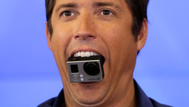 GoPro's CEO Nick Woodman holds a GoPro camera in his mouth as he celebrates his company's IPO at the Nasdaq MarketSite in New York, Thursday, June 26, 2014. GoPro, the maker of wearable sports cameras, loved by mountain climbers, divers, surfers and other extreme sports fans, said late Wednesday it sold 17.8 million shares at $24 each in its initial public offering of stock. (AP Photo/Seth Wenig) ORG XMIT: NYSW101