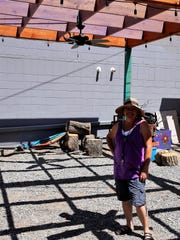 Studio 116 owner Karen Ellsbury stands under the pergola