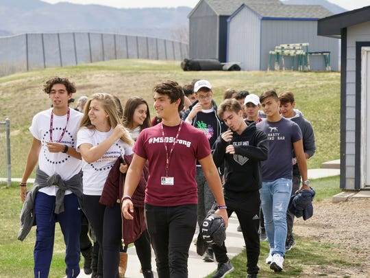 Wearing a maroon shirt that says #MSDStrong, Gabriel Motta, a 10th grader who survived the Feb. 14 shooting at Marjory Stoneman Douglas High School in Parkland, Fla., walks with classmates into Columbine High School on Thursday afternoon.