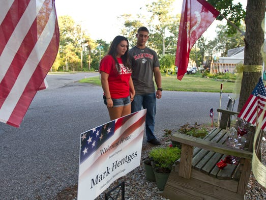 Lance Corporal Mark Hentges, United States Marine Corps, returned to his home in Brick after a deployment to Afghanistan and found his neighborhood covered with American flags. Hentges stands with his girlfriend Marissa Telerico looking over a bench in front of the house decorated with flags.  Brick, NJ Thursday, June 26, 2014 Doug Hood/Staff Photographer