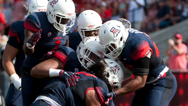 Oct. 10, 2015; Tucson; Arizona Wildcats defensive lineman Anthony Fotu (bottom) is congratulated by teammates after an interception during the second quarter against the Oregon State Beavers at Arizona Stadium.