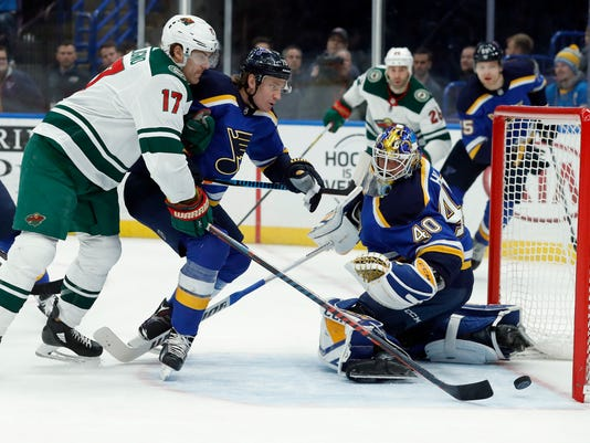 Minnesota Wild's Marcus Foligno (17) scores past St. Louis Blues goaltender Carter Hutton (40) and Jay Bouwmeester, center, during the first period of an NHL hockey game Tuesday, Feb. 6, 2018, in St. Louis. (AP Photo/Jeff Roberson)