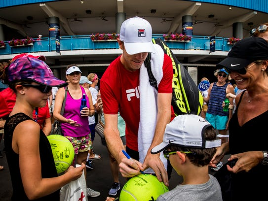 Sam Querrey signs tennis ball after practicing at the