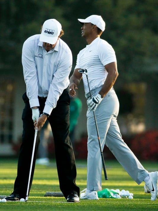 Phil Mickelson, left, and Tiger Woods warm up on the driving range during practice for the Masters golf tournament at Augusta National Golf Club, Tuesday, April 3, 2018, in Augusta, Ga. (AP Photo/Charlie Riedel)