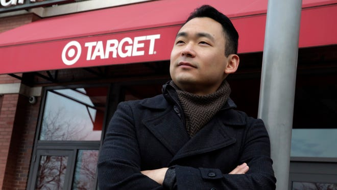 Identity theft victim Mark Kim poses for photos in front of a Target store, in the Brooklyn borough of New York. Kim spent seven months trying to clear his credit history after his personal information was compromised in a data breach at Target last year.