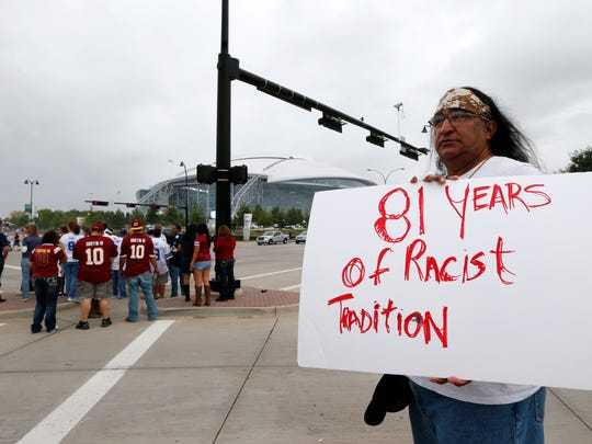 Juan Mancias, of Floresville, Texas, a member of the American Indian Movement of Central Texas, holds a sign as he joins others in protest before a game between the Redskins and Cowboys.