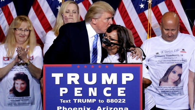 Republican presidential candidate Donald Trump hugs a woman, whose child was killed by a person living in the country without legal permission, after delivering an immigration policy speech during a campaign rally at the Phoenix Convention Center, Wednesday, Aug. 31, 2016, in Phoenix.