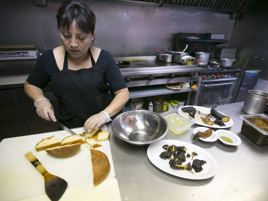 Chef and owner Elizabeth Hernandez cuts bread for the