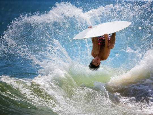Carter Hill,16, flips over the waves doing a barrel roll during practice at Dewey Beach as he prepares to compete at The Zap World Championship of Skimboarding in Dewey Beach this weekend.
