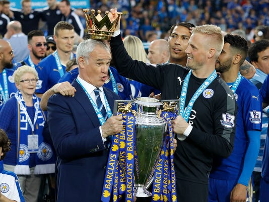 Leicester's team manager Claudio Ranieri gets a crown by Leicester's goalkeeper Kasper Schmeichel  as they lift the trophy as Leicester City celebrate becoming the English Premier League soccer champions at King Power stadium in Leicester, England, Saturday, May 7, 2016.(AP Photo/Matt Dunham)