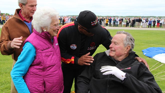 In this photo provided by the All Veteran Parachute Team, former President George H.W. Bush (right) is congratulated on his parachute jump by his son, former President George W. Bush (far left), his wife Barbara Bush and his tandem team partner Mike Elliott on his 90th birthday in Kennebunkport, Maine, Thursday, June 12, 2014.
